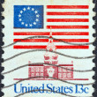 Royalty-Free Stock Photo: USA - CIRCA 1975: A stamp printed in USA shows 13 star flag over Independence Hall, circa 1975.