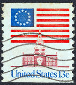 USA - CIRCA 1975: A stamp printed in USA shows 13 star flag over Independence Hall, circa 1975. — Photo