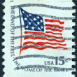 "Stock Photo: US- CIRC1975: stamp printed in USfrom ""Americana"" issue shows Fort McHenry flag and inscription ""Land of Free-Home of Brave"", circ1975."