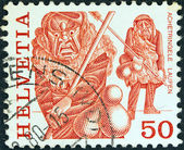"SWITZERLAND - CIRCA 1977: A stamp printed in Switzerland from the ""Regional Folk Customs"" issue shows Archetringele, Laupen, circa 1977. — Stock Photo"
