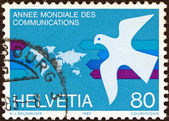 SWITZERLAND - CIRCA 1983: A stamp printed in Switzerland issued for the World Communications Year shows Carrier pigeon and world map, circa 1983. — Stock Photo