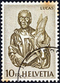 "SWITZERLAND - CIRCA 1961: A stamp printed in Switzerland from the ""Wood Carvings from St. Oswald's Church, Zug"" issue shows apostle Luke, circa 1961. — Stock Photo"