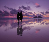 Silhouette of a romantic happy couple on a beach at sunset — Stock Photo