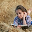 Country girl reading book lying at haystack — Stock Photo #11326067