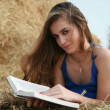Country girl with book lying at haystack looking to camera — Stock Photo #11326068