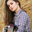Stock Photo: Country girl with guitar sitting at haystack