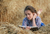 Country girl reading book lying at haystack — Stock Photo