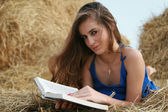Country girl with book lying at haystack looking to camera — Stock Photo