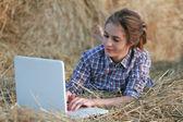 国の女の子は干し草の山の上に横たわるラップトップ上で入力 — ストック写真
