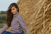 Country girl sitting at haystack half-turned looking to camera — Stock Photo