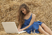 Girl in blue dress typing on laptop — Stock Photo