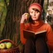 Stock Photo: Young woman holding apple and reading book in fall park