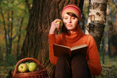 Young woman holding apple and reading book in fall park — Stock Photo