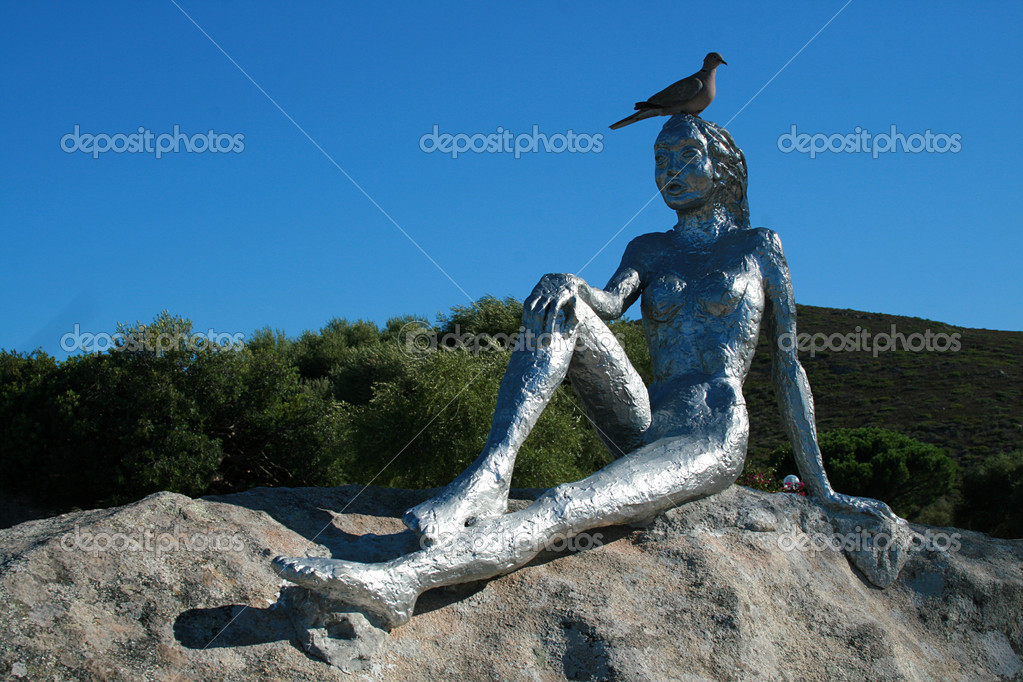 A dove rests on the head of a statue. The statue shows a woman sunbathing.  Stock Photo #11308645