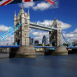 London Tower Bridge with colorful flag of England - Stock Photo