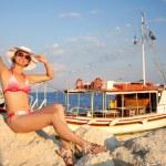 Beautiful happy woman in bikini with boat in harbor — Stock Photo #11108264