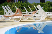 Pretty woman relaxing near the swimming pool — Stock Photo