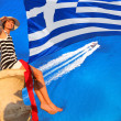 Sexy woman on the rock above azure sea with Greece flag — Stock Photo
