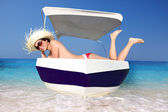 Sexy young Woman relaxing on motor boat against azure sea — Stock Photo