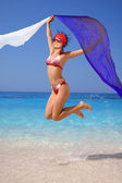 Happy Girl jumping on the beach with scarfs — Стоковое фото