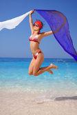šťastná dívka, která skočila na pláži s šátky — Stock fotografie