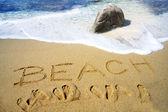 Beach handwritten in sand on a beac — Stock Photo
