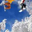 Foto Stock: Snowboarders jumping against blue sky