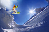 Snowboarder jumping against blue sky — 图库照片
