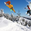 Snowboarders jumping against blue sky - ストック写真