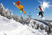Snowboarders jumping against blue sky — Stock Photo