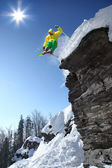 Skier jumping though the air from the cliff — Stock fotografie