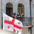 Stock Photo: Young men watch military parade from balcony. Tbilisi, Georgia.