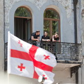 Young men watch military parade from balcony. Tbilisi, Georgia. — Stock Photo
