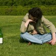 Drunk man on a meadow — Stock Photo
