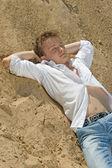 Yong man sleep on sand — Stock Photo