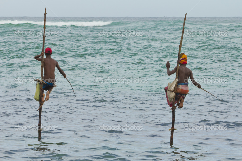 2 fishermen on sticks in the middle of the sea — Stock Photo #11851418