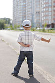 Boy hitching on road — Stock Photo