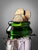 Champagne bottle and coins — Stock Photo