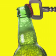 Opening beer bottle with metal opener — Stock Photo