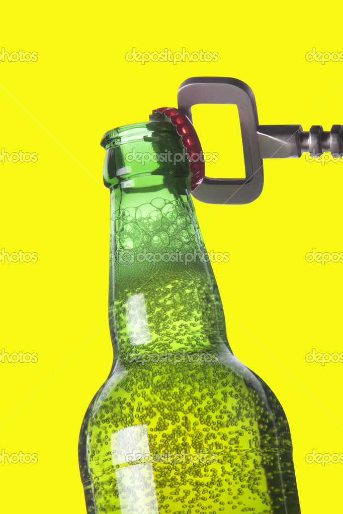 Opening beer bottle with metal opener on a yellow — Stock Photo #11041546