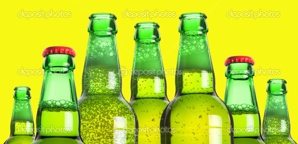 Row of beer bottleson a yellow background — Stock Photo #11041564