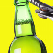 Stock Photo: Opening beer bottle with metal opener