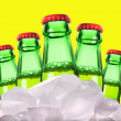 Beer bottles with ice on a yellow background - Stock Photo