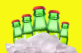 Beer bottles with ice on a yellow background — Stock Photo