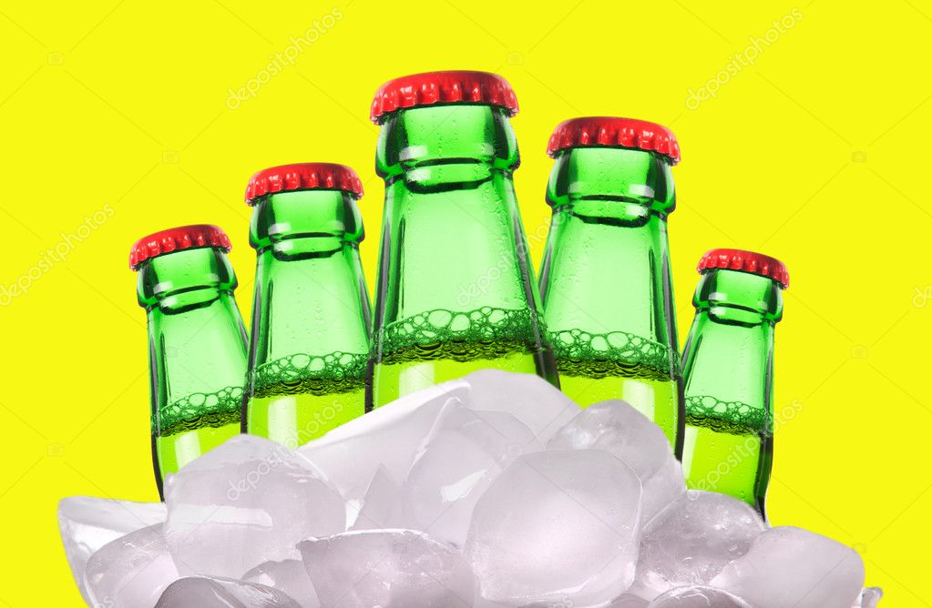 Beer bottles with ice isolated on a yellow background — Photo #11160024