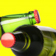 Green beer bottles with red caps isolated on a yellow — Stock Photo