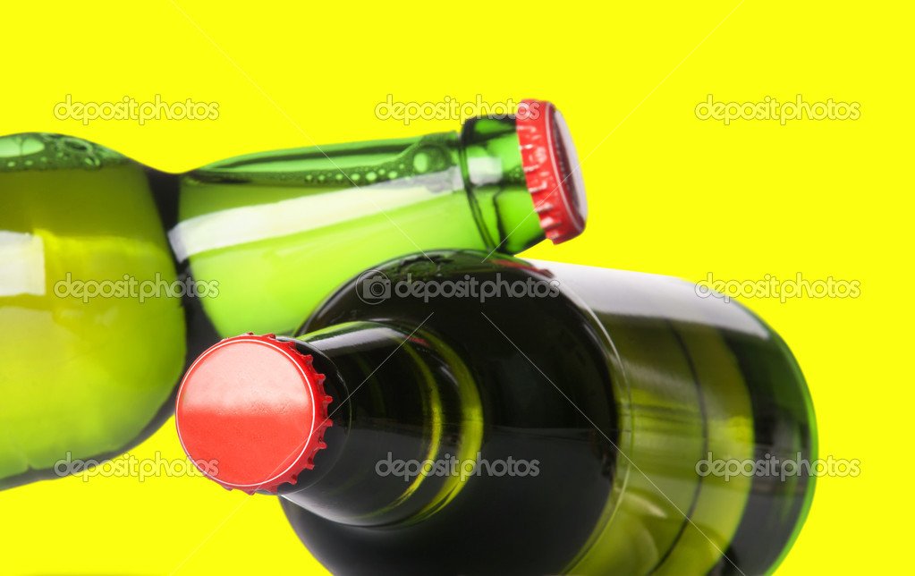 Green beer bottles with red caps isolated on a yellow background — Lizenzfreies Foto #11307419