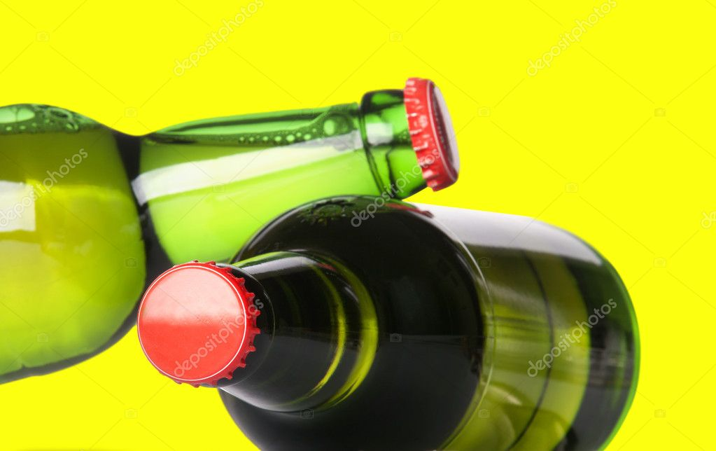 Green beer bottles with red caps isolated on a yellow background — Foto Stock #11307419