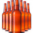 Stock Photo: Row of beer Bottles with drops isolated