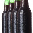 Row of dark beer Bottles with drops isolated — Stock Photo